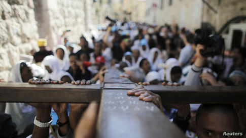 Christian worshippers carry a cross during a procession along the Via Dolorosa on Good Friday during Holy Week in Jerusalem's Old City.