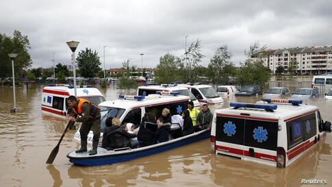 A man rows a boat past flooded ambulance vehicles in the flooded town of Obrenovac, southwest of Belgrade, Serbia, May 17, 2014.