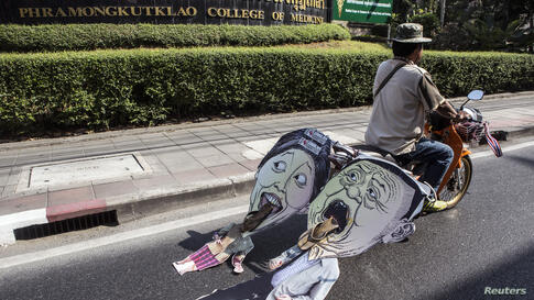 An anti-government protester pulls a caricature of Thailand's Prime Minister Yingluck Shinawatra and her brother Thaksin as he rides during a rally in central Bangkok.