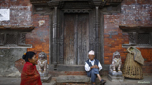 A man sits at the doorway of a temple along the streets in the ancient city of Bhaktapur, near Nepal's capital Kathmandu.