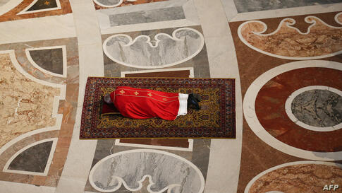 Pope Francis lies on the floor as he prays during the Celebration of the Lord's Passion on Good Friday at St Peter's Basilica at the Vatican.