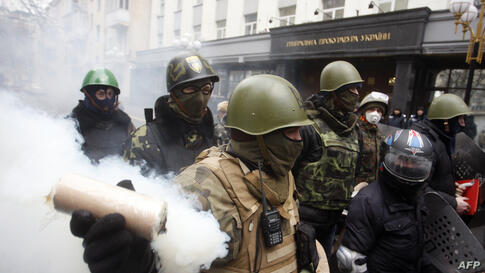 A man holds a smoke bomb as anti-government protesters take part in a protest rally in front of the Prosecutor General building in Kyiv, Ukraine. Protesters armed with shields and clubs demanded the government stop prosecuting cases against anti-govern...