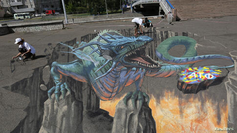 """U.S. artist Tracy Lee Stum (L) and her assistants work on the """"Singing Dragon"""" interactive 3-D street painting as they take part in the 4th Krasnoyarsk International Music Festival of the Asian-Pacific region in central Krasnoyarsk, Siberia, Russia."""