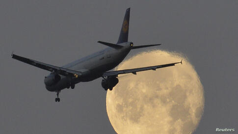 A passenger plane flies past the moon on its final descent to Heathrow Airport in London, Britain.