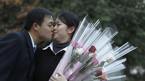 Chung Chen-han (L), 28, kisses Tsai Yong-chen, 27, after she accepted his wedding proposal on Valentine's Day in Taipei, Taiwan, February 14, 2012. (REUTERS)