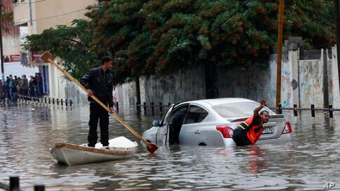 Palestinian rescue members pulls a car stranded on a flooded street after heavy raining in Gaza City.