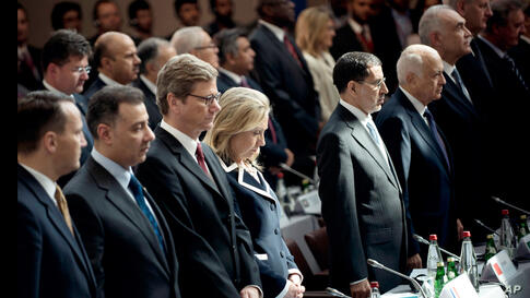 """Clinton stands with other delegates during a minute of silence at the """"Friends of Syria"""" meeting, in Paris, July 6."""