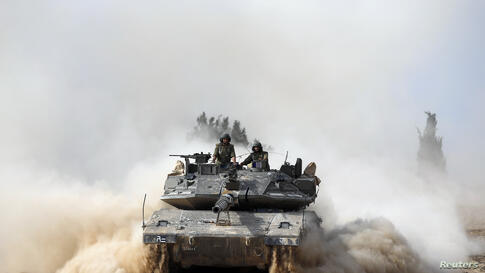 Israeli soldiers ride atop a tank outside the southern Gaza Strip. Israel launched a series of air strikes on Gaza to quell Hamas rocket fire, and the Islamist group's armed wing said seven of its gunmen were killed.
