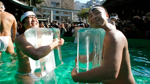 Japanese physical fitness enthusiasts hold blocks of ice while standing in cold water at Teppozu Inari Shinto shrine during a winter ritual to keep themselves fit and to display their perseverance in Tokyo.