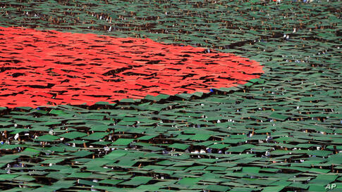Bangladeshis flip colored cards to form the national flag during Victory Day celebrations in Dhaka.