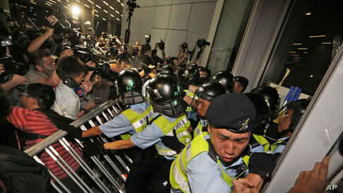 Police officers clash with the protesters breaking into the Legislative building during a demonstration in Hong Kong. Hundreds of villagers and students protested against the government on a development plan in the North Eastern New Territories.