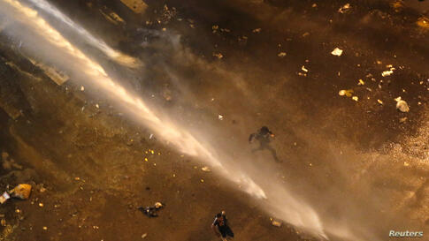 Anti-government protesters run away from a water cannon shot by the national guard during a protest at Altamira Square in Caracas, Venezuela, Mar. 14, 2014.