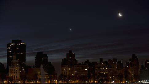A crescent moon and Venus (L) rise in the pre-dawn hours over the east side of Manhattan in New York.