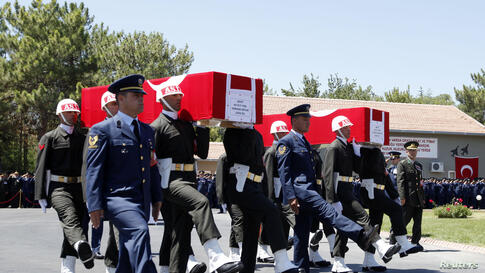 Turkish soldiers carry the coffins of fallen Turkish pilots, Captain Gokhan Ertan and Lieutenant Hasan Huseyin Aksoy, during an official farewell ceremony at the 7th Jet Main Air Base in the eastern Turkish city of Malatya July 6, 2012.