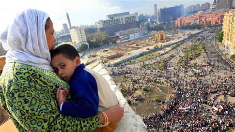 An Egyptian mother hugs her child as she watches some thousands of Egyptian protesters gather in Tahrir Square. (Amr Nabil/AP)