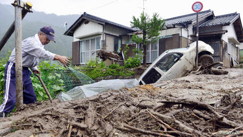 A man clears debris at an area affected by a landslide caused by Typhoon Neoguri in Nagiso town, Nagano prefecture, Japan, in this photo taken by Kyodo.