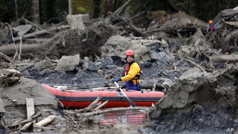 A searcher uses a small boat to look through debris from a deadly mudslide in Oso, Washington, USA, Mar. 25, 2014. At least 24 people were killed in the 1-square-mile slide that hit in a rural area about 55 miles northeast of Seattle on Mar. 23. Severa...