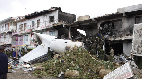 A pile of mild stimulant drug Khat lies beside the wreckage of a Fokker 50 cargo plane after it crashed into a building after takeoff at Kenyatta International Airport, in Nairobi, Kenya.