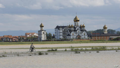 A man drives his bicycle away from a flooded area in the village of Dvorovi, near Bijeljina, Bosnia-Herzegovina, May 17, 2014.