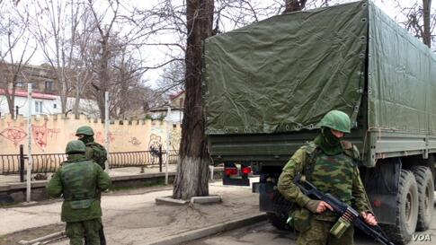 Soldiers without insignia guard buildings in the Crimean capital, a day after the Crimean prime minister called for Russian help, Simferopol, Ukraine, March 2, 2014. (Elizabeth Arrott/VOA).