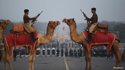India's Border Security Force (BSF) soldiers ride their camels during a rehearsal for the 'Beating the Retreat' ceremony in New Delhi, India, Jan. 24, 2014.