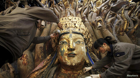 Restoration workers peel off loose gold foil as part of a restoration project for an 800-year-old Thousand-Hand Guanyin Buddhist statue on Mount Baoding in Chongqing municipality, China. The stone-carving statue, which takes up about 88 square metres o...