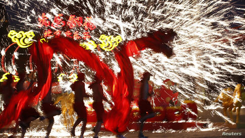 Dancers perform a fire dragon dance in the shower of molten iron spewing firework-like sparks during a folk art performance at the Happy Valley amusement park in Beijing, China, to celebrate the traditional Chinese Spring Festival on the first day of t...