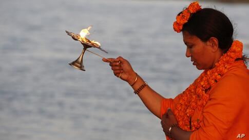 Mahant Trikaal Bhawanta, leader of the first group of women sadhvi, or Hindu holy women, performs evening rituals on the banks of River Yamuna in Allahabad, India.