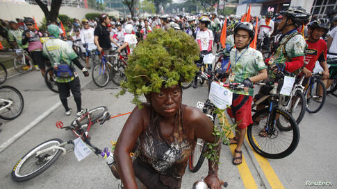 A costumed woman rides her bike during the 15th tour of the fireflies in Pasig city, metro Manila, Philippines. The annual tour of the fireflies advocates clean air and healthy living by promoting bicycles as the main mode of transportation. This year'...