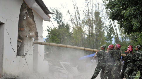 Paramilitary policemen demolish a building after an earthquake hit Yingjiang county, Yunnan province, May 24, 2014. At least 13 people were injured after a 5.6-magnitude earthquake jolted Yingjiang county in southwest China, Xinhua News Agency reported.