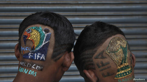 Indian soccer fans pose for a picture after getting their hair cut by Indian hair stylist Rabin Das outside his saloon on the outskirts of Kolkata, ahead of the 2014 World Cup in Brazil. Das charges 500 rupees ($8) for a FIFA World Cup trophy haircut.