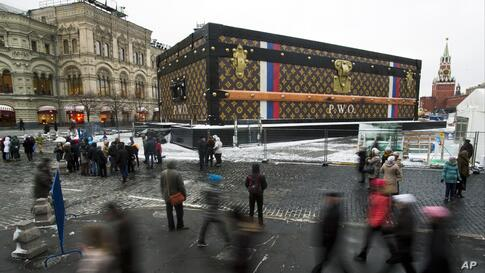 Tourists and visitors pass by a two-story Louis Vuitton suitcase erected at the Red Square in Moscow, Russia. Politicians didn't like it, the public didn't like it, so the gigantic Louis Vuitton suitcase is being booted out of Red Square. The GUM depar...