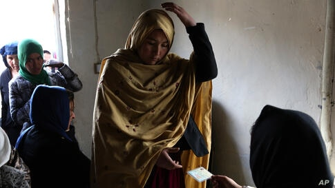 An Afghan woman receives her voter registration card from an employee of the Afghan Independent Election Commission at a women's voter registration center in Kabul, Afghanistan.