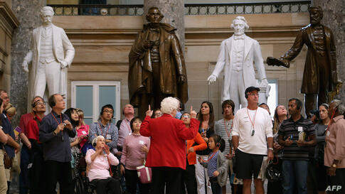A Capitol Guide Service employee leads a group of tourists through Statuary Hall at the U.S. Capitol in Washington, DC. If Congressional Republicans and Democrats do not find common ground with President Obama on the federal budget then at midnight lar...