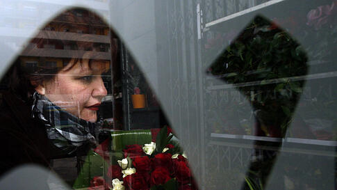 A woman holds roses on Valentine's Day at a flower shop in Tirana, Albania February 14, 2012. (REUTERS)