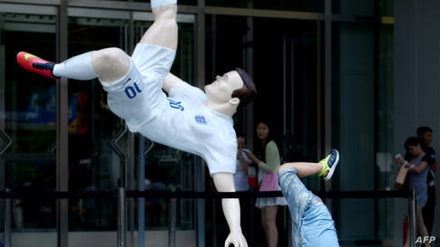 A boy poses for a photo in front of a large figure of England football player Wayne Rooney at the entrance of a mall in Beijing, China.