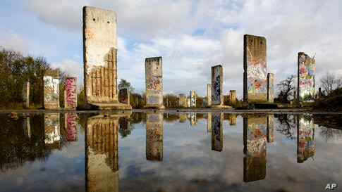 On the eve of the 24th anniversary of the fall of the Berlin Wall, original pieces of the Berlin Wall are mirrored in a pond as they are are displayed for sale at the city of Teltow near Berlin, Germany.