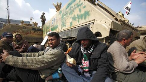 A protester reads the Quran as they gather around army vehicles at Tahrir Square in Cairo, February 7, 2011