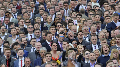 "Race goers react during racing on ""Ladies' Day"", the second day of the Grand National horse racing meeting at Aintree, northern England."