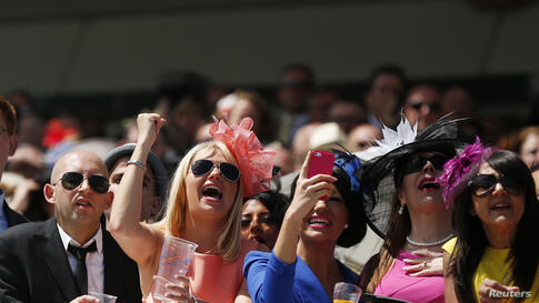 Racegoers react during the third race of Ladies Day in the Royal Enclosure at the Epsom Derby Festival in Epsom, southern England.