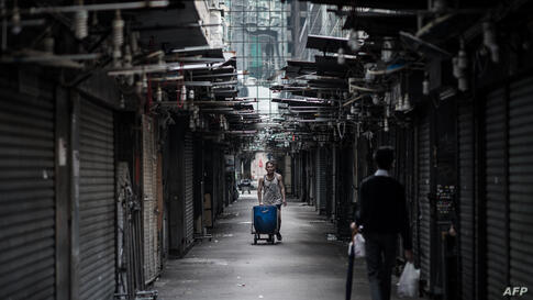 A man pushes his handcart in a street market in Hong Kong. It's a simple contraption - an iron frame, foldout handle and four rubber wheels - but in Hong Kong the old-fashioned handcart is what keeps the city rolling.