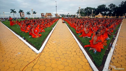 Buddhist monks sit on the grass as they pray in front of the Royal Palace during a ceremony in Phnom Penh, Cambodia. A three-day royal procession to take the remains of late Cambodian King Norodom Sihanouk from the cremation site to the Royal Palace be...