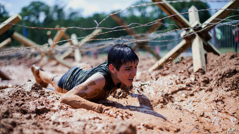 A boy crawls through mud at the inaugural Battlefrog Obstacle Course Race Series held at Georgia International Horse Park, in Conyers, Georgia, May 31, 2014.