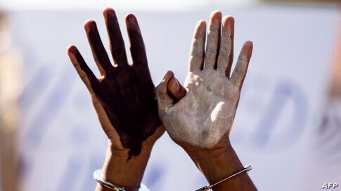 An African asylum seeker, who entered Israel illegally via Egypt, uses handcuffs and raises up his hands painted in black and white during a protest in front of the Israeli Interior Ministry in the Mediterranean coastal city of Tel Aviv after several d...