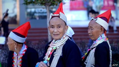 Women dressed as ethnic minorities on a business street in Beijing. The seven-day holiday built around China's National Day on October 1 sees millions of members of China's newly wealthy and mobile middle-class travel locally and abroad.