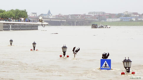 A traffic sign and the tips of street lamps are seen in floodwaters as a riverside street is submerged by an overflowing river after heavy rainfalls hit Lanxi, Zhejiang province, China, June 22, 2014.
