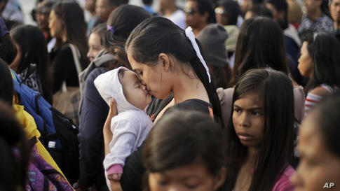 A Typhoon Haiyan survivor kisses her baby as she waits to board her evacuation flight at the airport in Tacloban, Philippines.