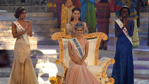 New Miss World, Megan Young (C) from the Philippines is crowned by outgoing Miss World Yu Wenxia after winning the crown as first runner up, Marine Lorphelin (L) of France and second runner up Carranzar Naa Okailey (R) from Ghana look on during the Mis...