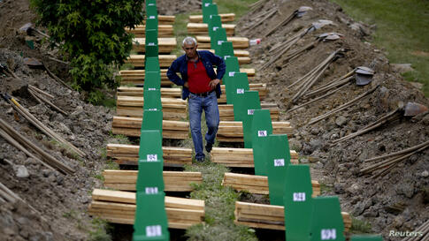A Bosnian Muslim man searches for the coffin of his relative, which is one of the 175 coffins of newly identified victims from the 1995 Srebrenica massacre, in the Potocari Memorial Center, near Srebrenica.