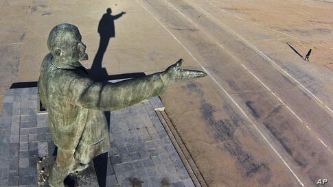 A woman walks past a statue of Soviet Union founder Vladimir Lenin at the Russian leased Baikonur cosmodrome in Kazakhstan.